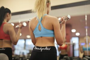 Person Showing Woman In Blue Sport Bra Carrying Gray Dumbbell